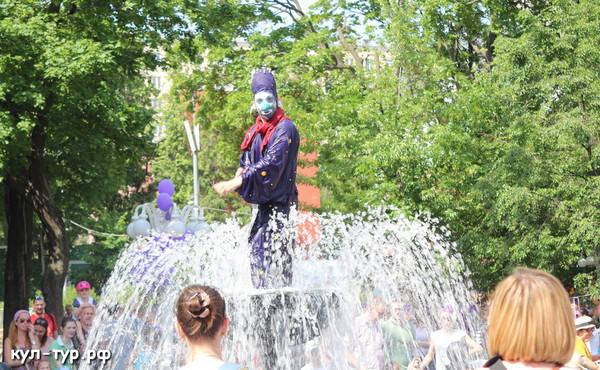 клоун играет с детьми в фонтане