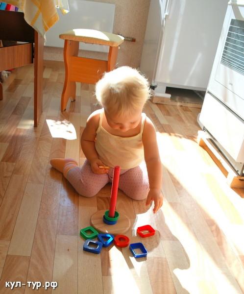 ребёнок собирает пирамидку