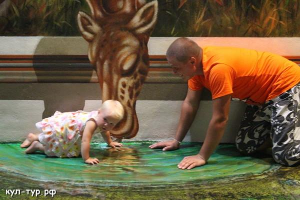 ребёнок играет с жирафом