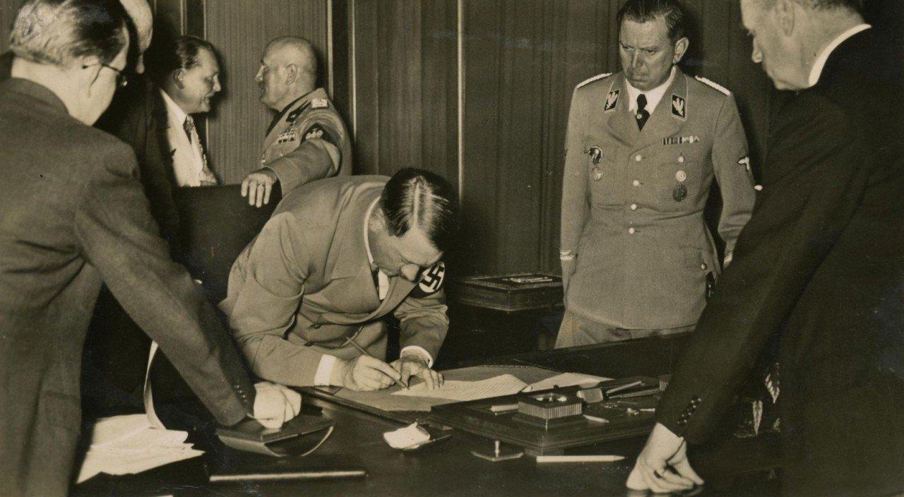 Адольф Гитлер подписывает Мюнхенское соглашение после переговоров