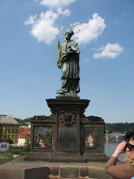Святой Ян Непомуцкий - самая старая и самая популярная из скульптур Карлова моста.<br/>Вокруг головы Непомуцкого — пять звезд, по преданию, появившиеся над водой<br/>в том месте, где его утопили