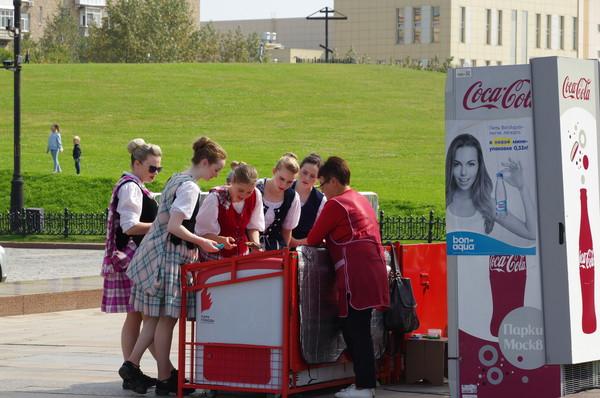 Девушки из международной команды исполнителей шотландских танцев выбирают московское мороженное