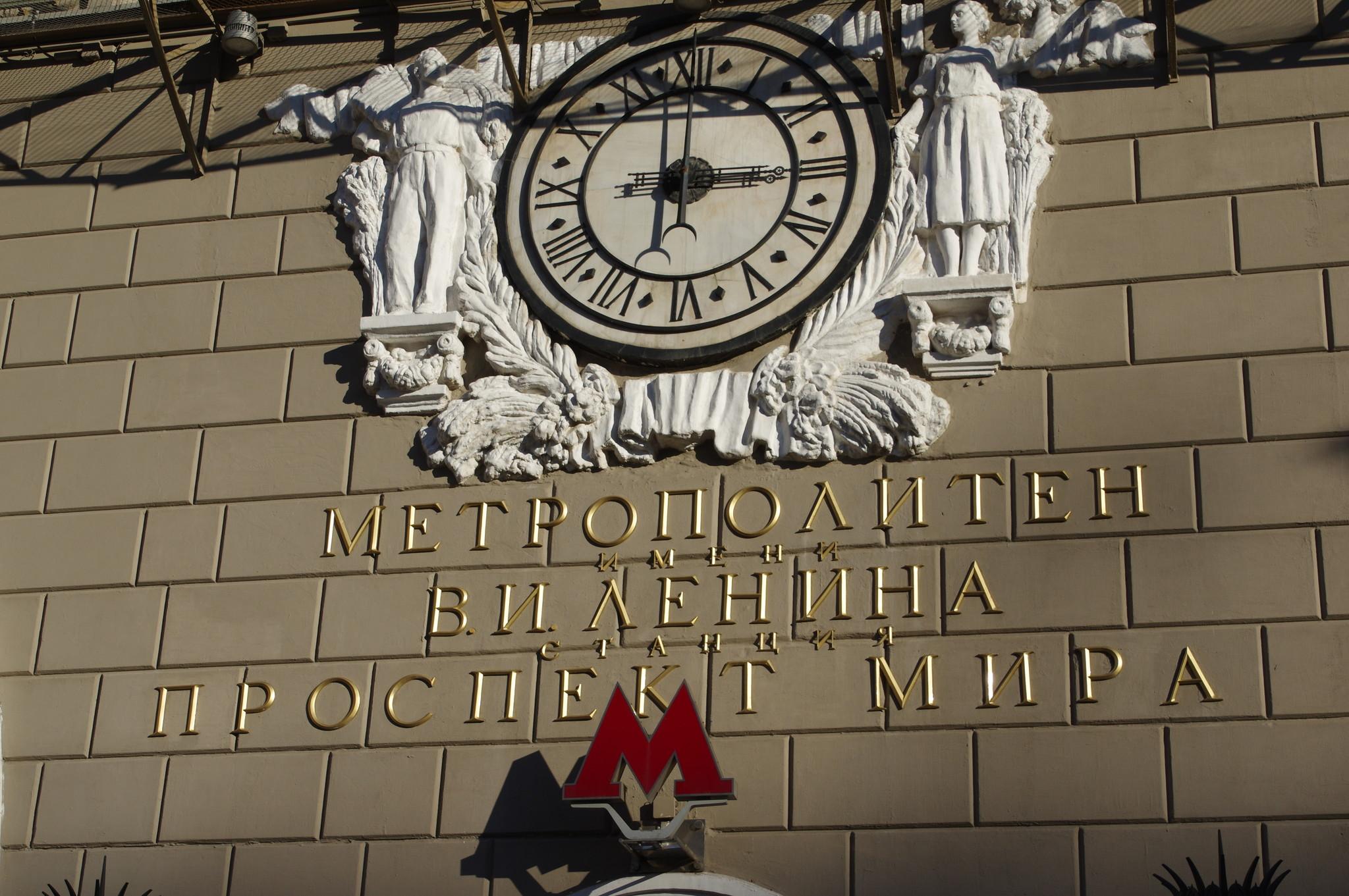 Часы, украшенные барельефом с изображением мужчины и женщины на фасаде наземного вестибюля станции «Проспект Мира» Кольцевой линии