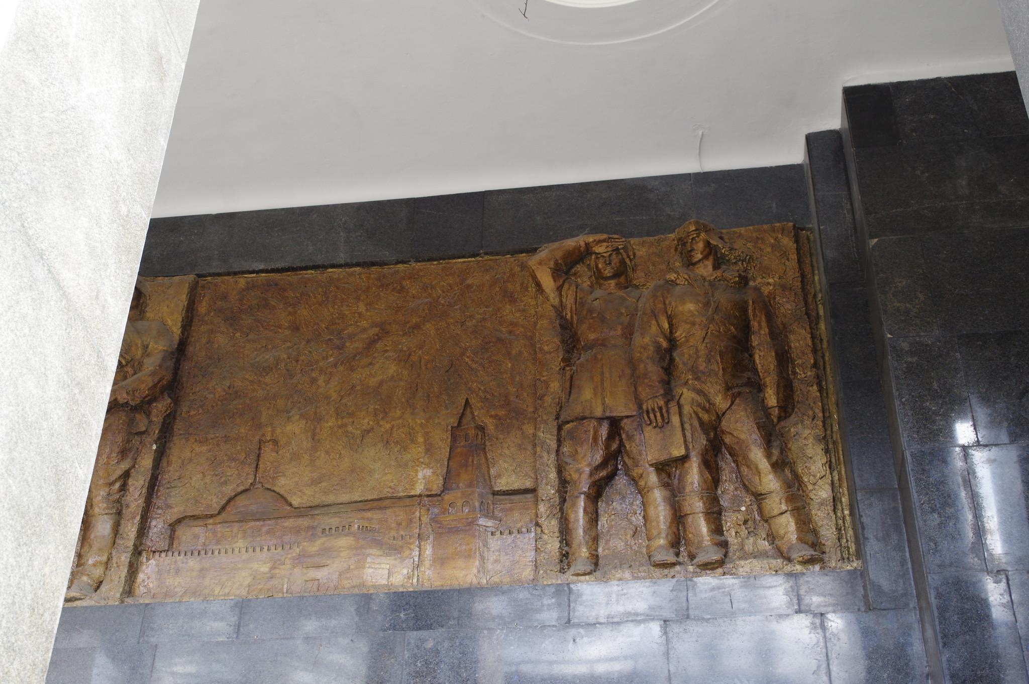Рельефные изображения панорамы Красной площади и солдат разных видов войск на фасаде вестибюля станции «Бауманская» Арбатско-Покровской линии