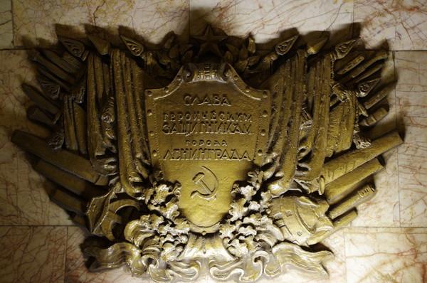 Металлический щит в обрамлении знамён, на котором написано «Слава героическим защитникам города Ленинграда», укреплён в центральном зале станции «Новокузнецкая» Московского метрополитена